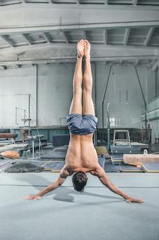Postura de equilíbrio de acrobacias ginástica homem caucasiano no ginásio