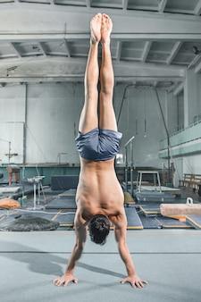 Postura de equilíbrio de acrobacias ginásticas de homem caucasiano na parede do ginásio