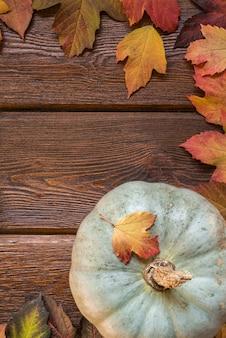 Postura plana com abóbora e folhas de outono armação de borda no fundo rústico de madeira escuro
