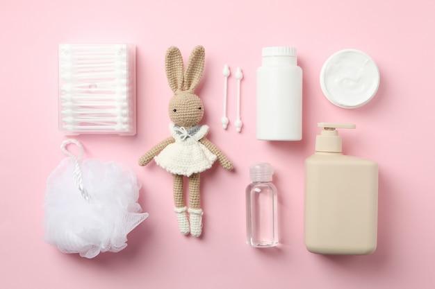 Postura plana com acessórios de higiene do bebê na parede rosa