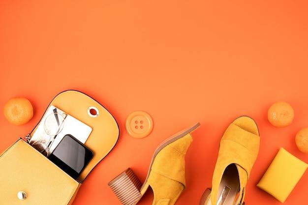 Postura plana com acessórios de moda feminina na cor amarela sobre parede texturizada de couro laranja. moda, blog de beleza online, estilo de verão, compras e conceito de tendências