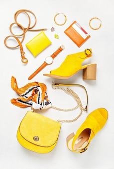 Postura plana com acessórios de moda mulher nas cores amarelas.