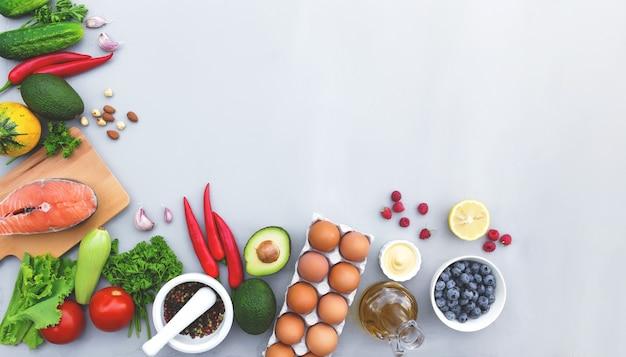Postura plana com alimentos diferentes, vegetais orgânicos, frutas biológicas, bagas, nozes, especiarias, ervas, azeite, ovos de galinha e uma xícara de peixe salmão. copie a área de espaço para algum texto. fundo cinza de concreto