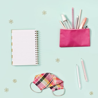 Postura plana com caderno e artigos de papelaria para menina, máscara de tecido rosa para proteção contra infecções.