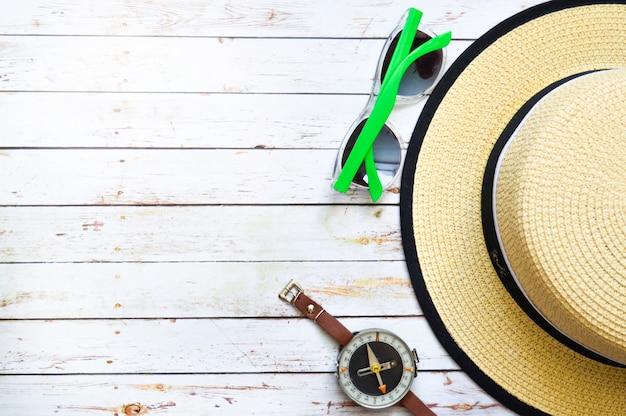 Postura plana com chapéu de palha, óculos de sol, bússola e estrela do mar