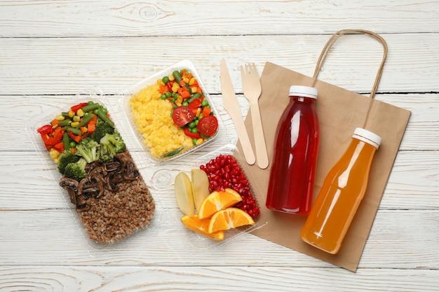 Postura plana com comida para viagem na parede de madeira. entrega de alimentos