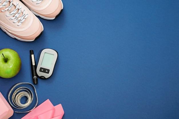 Postura plana com conceito de perda de peso dieta diabetes. tênis, fita métrica, glicosímetro em um azul