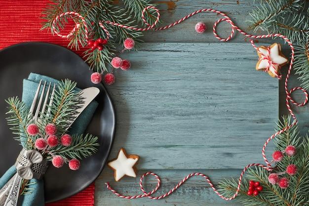 Postura plana com decorações de natal, bagas foscas e bugigangas e prato preto com louça
