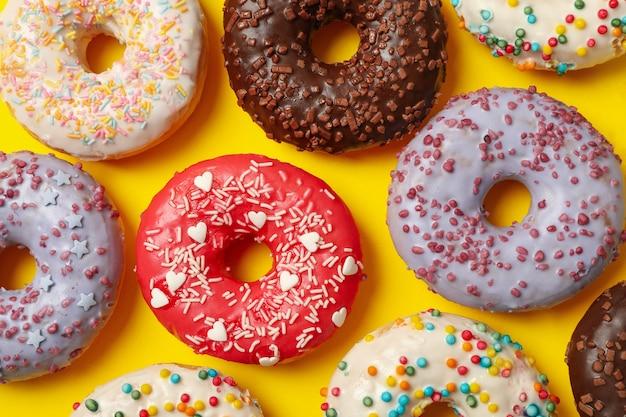 Postura plana com deliciosos donuts em fundo amarelo