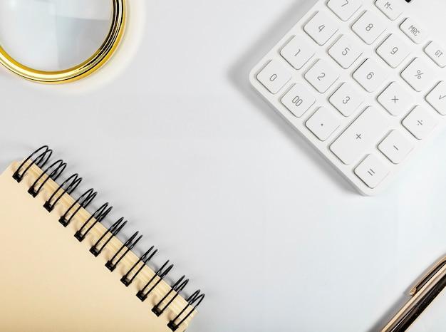 Postura plana com espaço de cópia em fundo branco com calculadora, lupa, bloco de notas, caneta.