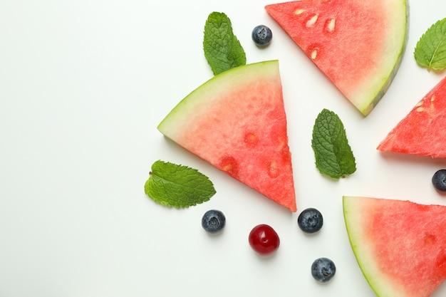 Postura plana com fatias de melancia e frutas no fundo branco