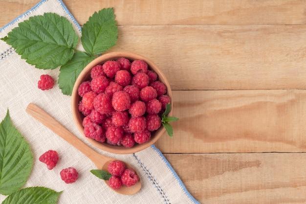 Postura plana com framboesas maduras e folhas no espaço da cópia da mesa de madeira deliciosas frutas orgânicas
