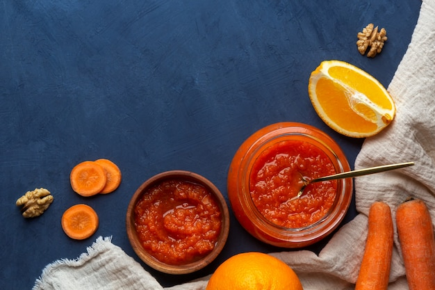 Postura plana com geléia de cenoura, nozes e laranjas sobre um fundo azul, vista superior, copie o espaço