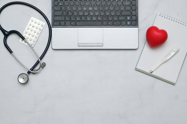 Postura plana com mesa médica com estetoscópio, caderno, material de escritório e espaço de cópia