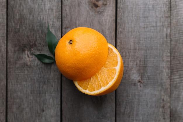Postura plana com metades frescas maduras fatiadas de frutas laranja em fundo cinza de madeira.