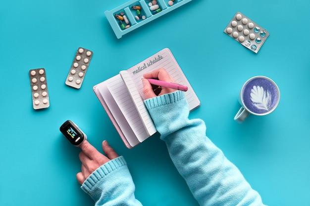 Postura plana com notebook com horário médico. mãos com caneta e oxímetro de pulso. vários comprimidos e caixa de comprimidos na parede azul de hortelã. monitorar quando tomar pílulas e vitaminas durante pandemias.
