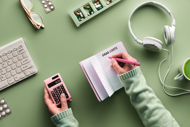 Postura plana com notebook para monitorar os custos dos medicamentos. mãos com caneta e calculadora. vários comprimidos e caixa de comprimidos na parede verde de hortelã. monitoramento de custos de vitaminas, medicamentos e suplementos alimentares.