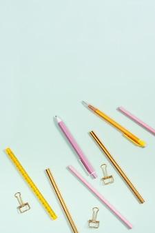 Postura plana com papelaria para escola ou escritório. lápis de cor rosa e dourado, canetas e clipes de metal.