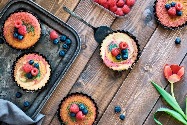 Postura plana com pequenos bolos de papagaio decorados com framboesa e mirtilo em madeira escura