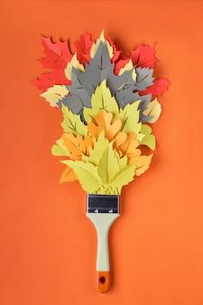 Postura plana com pincel carregado com tinta feita de folhas de outono decorativas em papel laranja