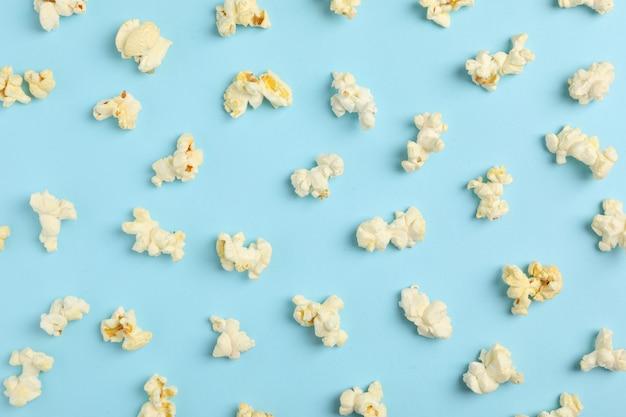Postura plana com pipoca no espaço azul. alimento para o cinema