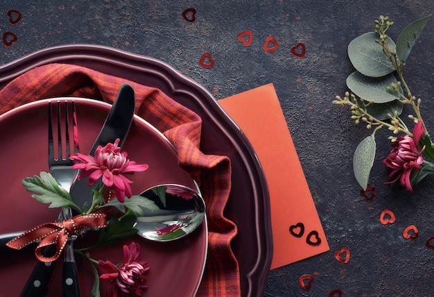 Postura plana com pratos de burgindy e louças decoradas com crisântemo de inverno, configuração de jantar de natal ou dia dos namorados