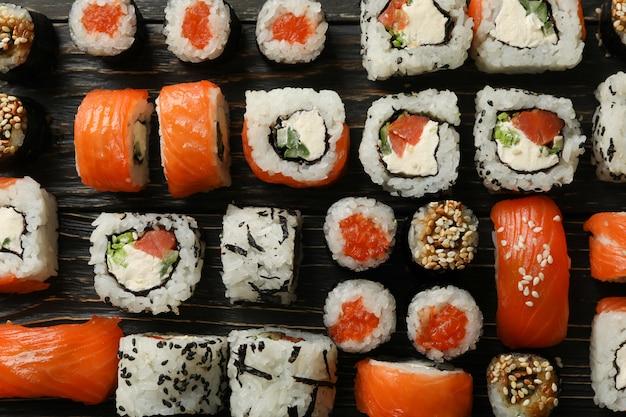 Postura plana com sushi rolls na mesa de madeira. comida japonesa