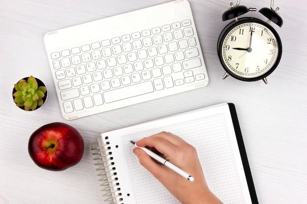 Postura plana com teclado branco, maçã, despertador e mão