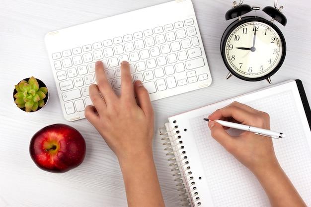 Postura plana com teclado branco, maçã, despertador e mãos