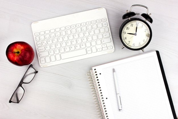 Postura plana com teclado branco, maçã, despertador e óculos
