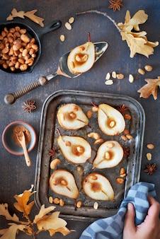 Postura plana com uma bandeja de peras assadas com nozes caramelizadas no fundo escuro de madeira com folhas de outono