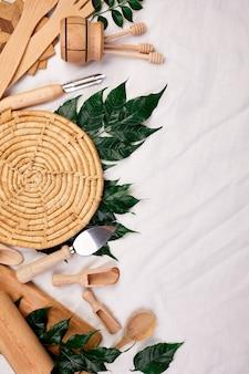 Postura plana com utensílios de cozinha de madeira com folhas verdes, utensílios de cozinha em fundo de têxteis, coleção ktchenware capturada de cima, maquete, quadro.