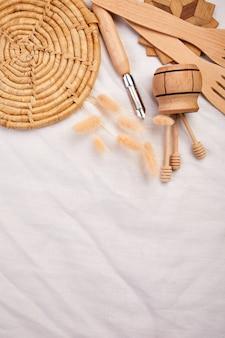 Postura plana com utensílios de cozinha de madeira, utensílios de cozinha em fundo de têxteis, coleção ktchenware capturada de cima, maquete, quadro.