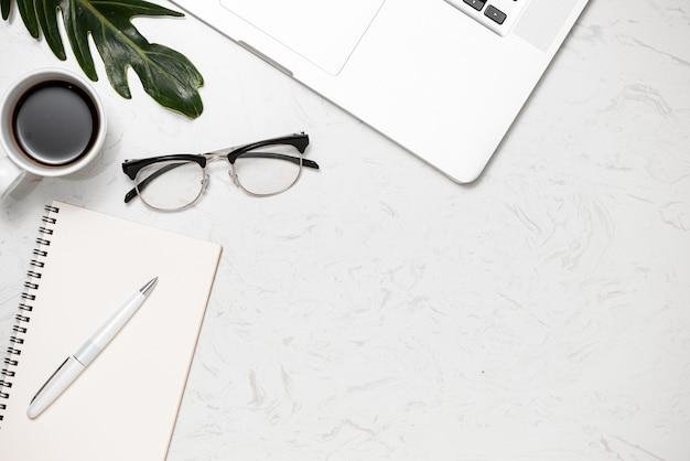 Postura plana criativa da mesa de trabalho. mesa de escritório com vista superior com laptop, xícara de café e teclado branco