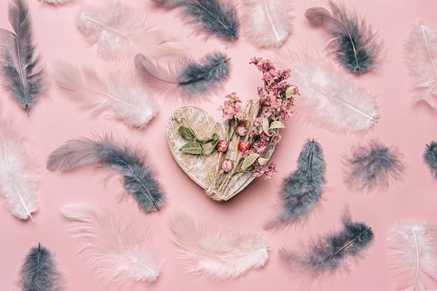 Postura plana criativa de coração de madeira em fundo de cor suave com plantas naturais e penas.