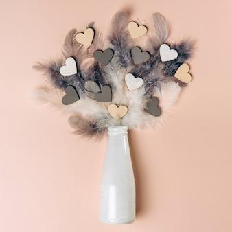 Postura plana criativa de corações de madeira e penas caindo da garrafa em um fundo de cor suave