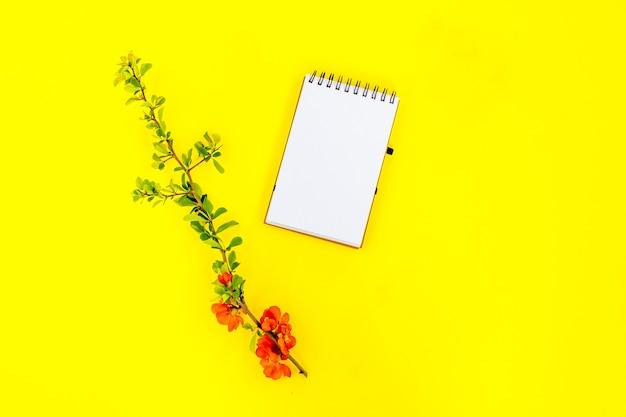 Postura plana criativa de simulação de quadro de bloco de notas espiral em branco e pétalas de flores de árvore de marmelo em fundo amarelo com espaço de cópia no estilo mínimo, modelo para letras, texto ou seu projeto.
