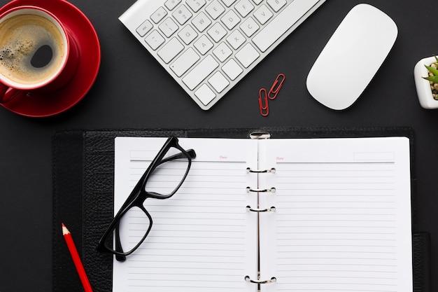Postura plana da agenda na mesa com teclado e café