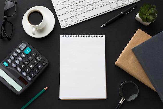 Postura plana da área de trabalho com notebook e agendas