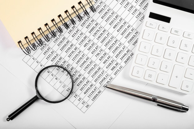 Postura plana da calculadora e documentos para relatório contábil de fluxo de caixa.