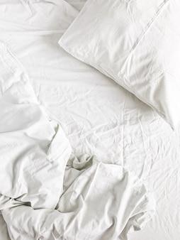 Postura plana da cama branca com travesseiros, cobertor e lençol. vista do topo