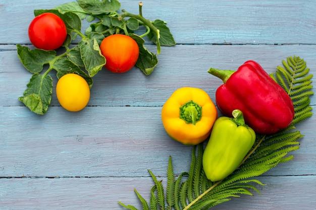 Postura plana da colheita sazonal de tomates, pimentões, vermelho, amarelo e verde, azul, fundo de madeira