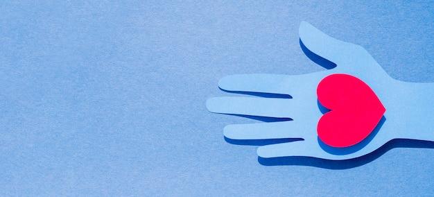 Postura plana da mão de papel segurando um coração com espaço de cópia