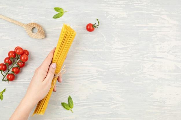 Postura plana da mão de uma mulher segurando espaguete e ingredientes para cozinhar macarrão italiano. espaguete, tomate, óleo, alho, parmesão. vista superior do conceito tradicional da culinária italiana