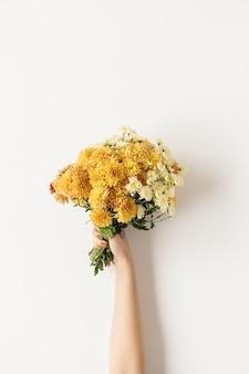 Postura plana da mão feminina segurando buquê de flores silvestres amarelo e gengibre cair em branco. vista do topo