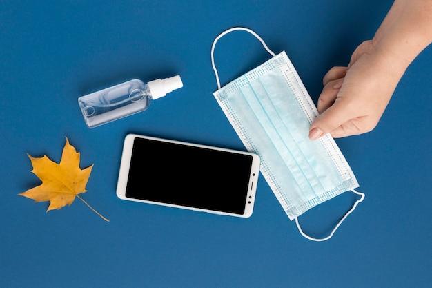 Postura plana da mão segurando uma máscara médica com smartphone e folha de outono