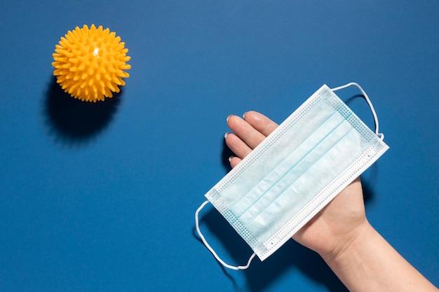 Postura plana da mão segurando uma máscara médica com vírus