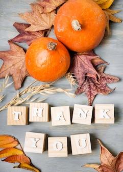 Postura plana da mensagem de ação de graças com folhas e elementos de outono