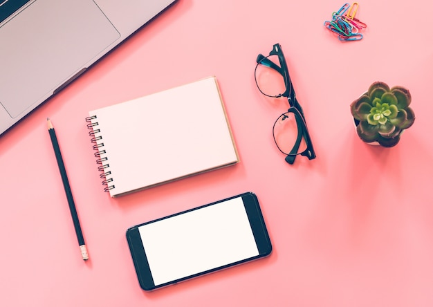 Postura plana da mesa do espaço de trabalho com laptop, caderno em branco, smartphone, lápis, artigos de papelaria com copyspace