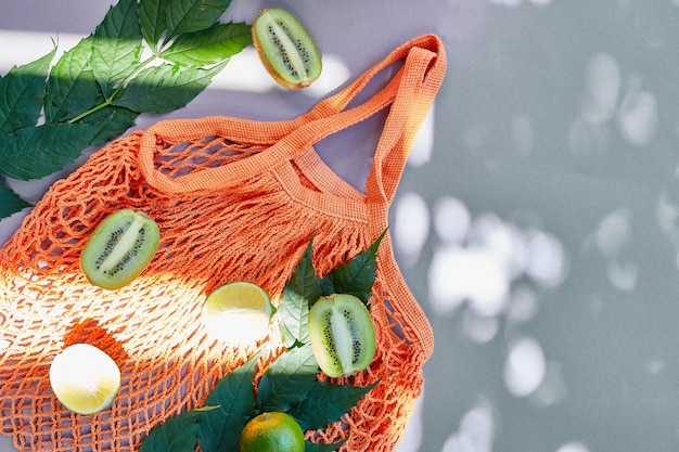 Postura plana da sacola de compras de malha ecológica com frutas, limão e kiwi na superfície cinza na luz solar, horário de verão. conceito de mercearia, cópia espaço, vista superior.